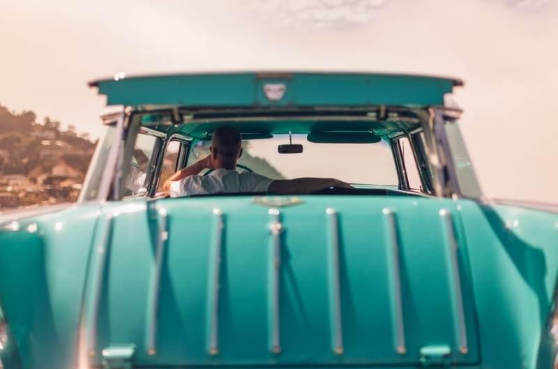 man driving turquoise car