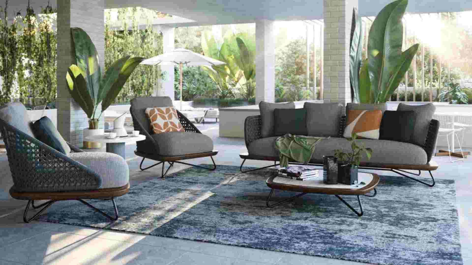 grey outdoor lounge on rug, large green plants