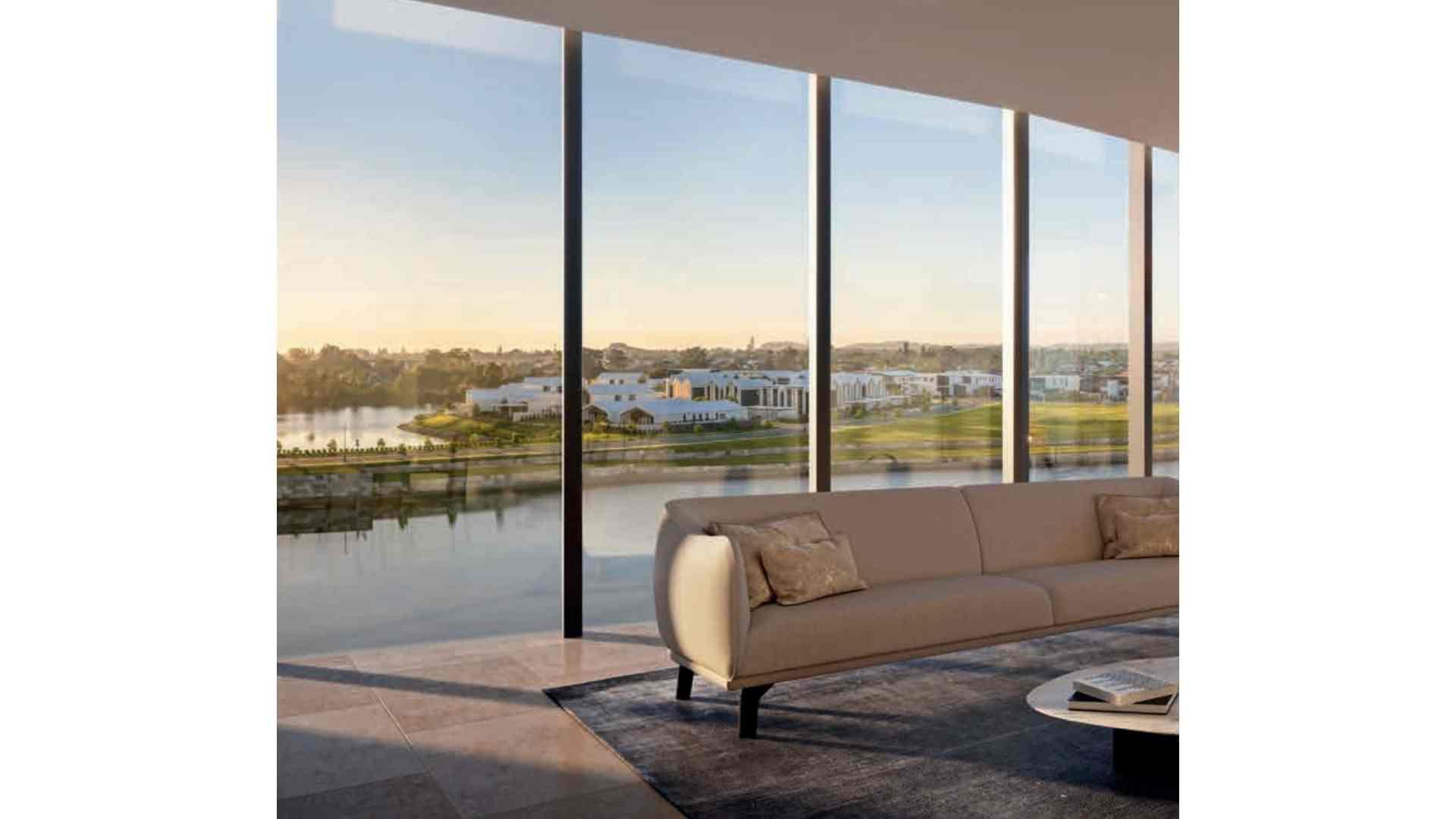 beige sofa on ash grey rug, living room floor to ceiling windows