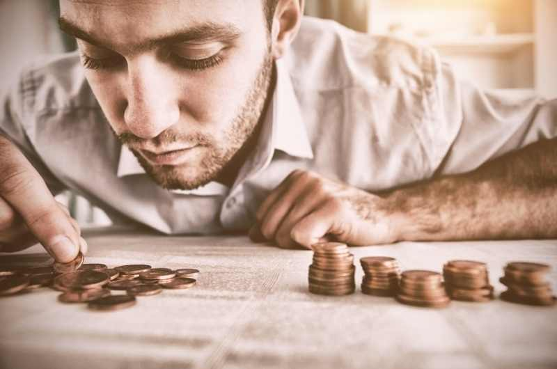 man counting coins and stacking them up